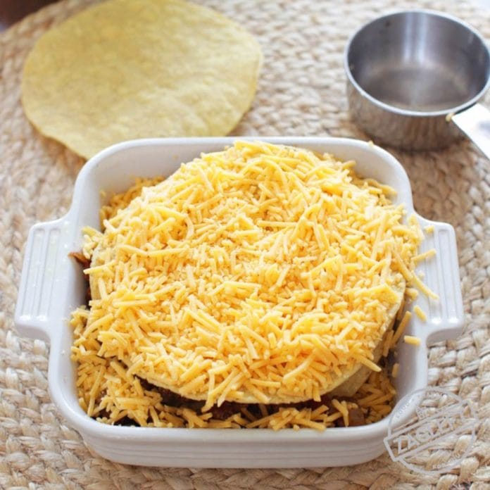 Taco Casserole For One - think of it as a Mexican Lasagna. Spicy ground beef and shredded cheddar cheese between crisp layers of crunchy tostadas and baked in the oven. Top with salsa, sour cream and black olives. An easy to assemble single serving recipe. onedishkitchen.com